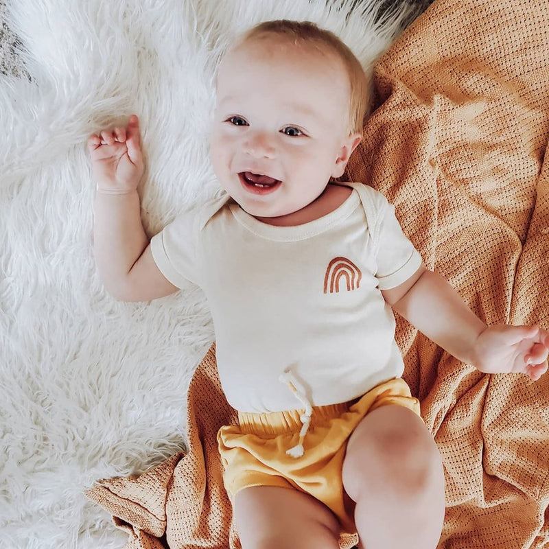 smiling baby boy laying down, wearing a bodysuit printed with a rust colored rainbow