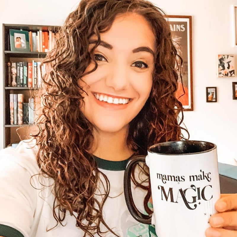 Smiling woman holding a mug with a black handle and black inside, printed with the words mamas make magic