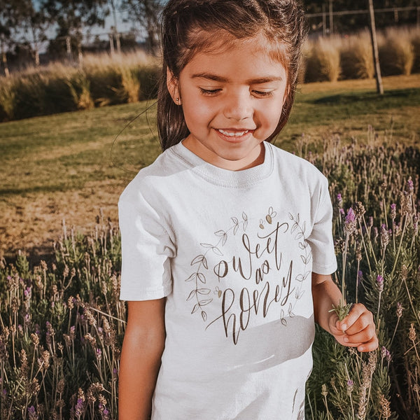 little girl wearing a white tee shirt printed with the words sweet as honey with leaves and bumblebees