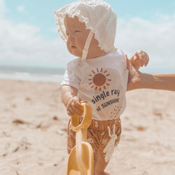 baby standing at the beach, wearing a sunhat, holding a yellow shovel, and wearing a white bodysuit printed with a sun and the words single ray of sunshine