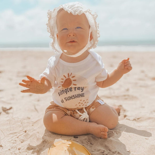 baby at the beach, wearing a sunhat, holding a yellow shovel, and wearing a white bodysuit printed with a sun and the words single ray of sunshine