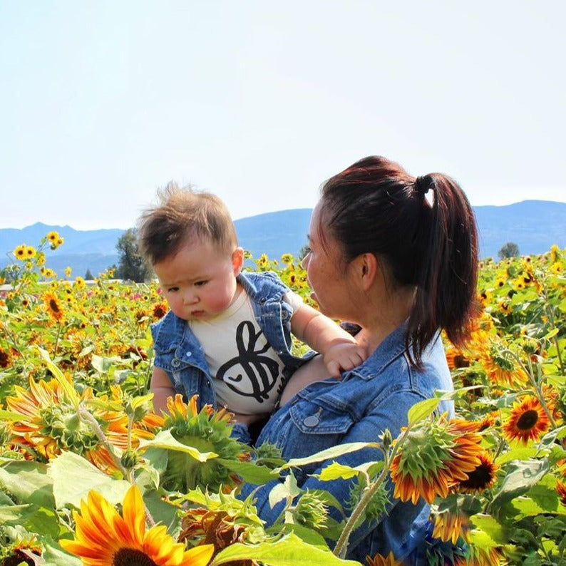 Mother holding her baby in a sunflower patch, the baby is wearing a bodysuit printed with a bee underneath a jean jacket vest