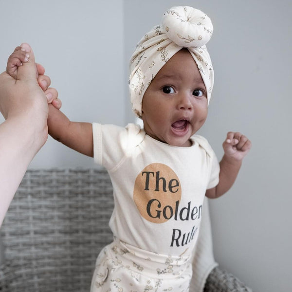 smiling baby girl wearing a floral print turban with matching pants, and a bodysuit printed with a golden sun and the words The Golden rule