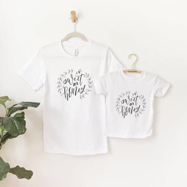 mommy and me white tee shirts hanging next to each other printed with the words sweet as honey with leaves and bumblebees