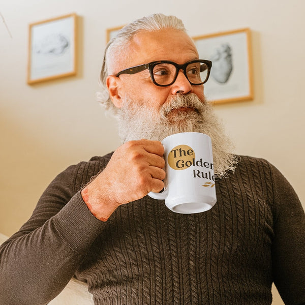 man drinking from a white coffee mug printed with the words The Golden Rule