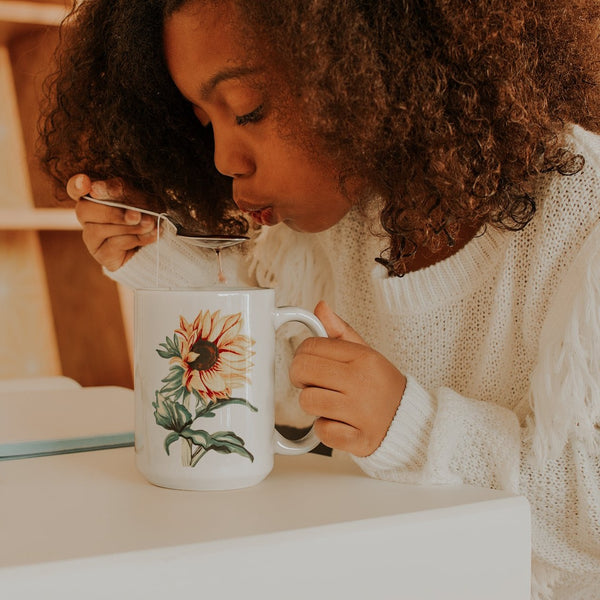 Little girl sipping tea out of a white mug printed with a sunflower