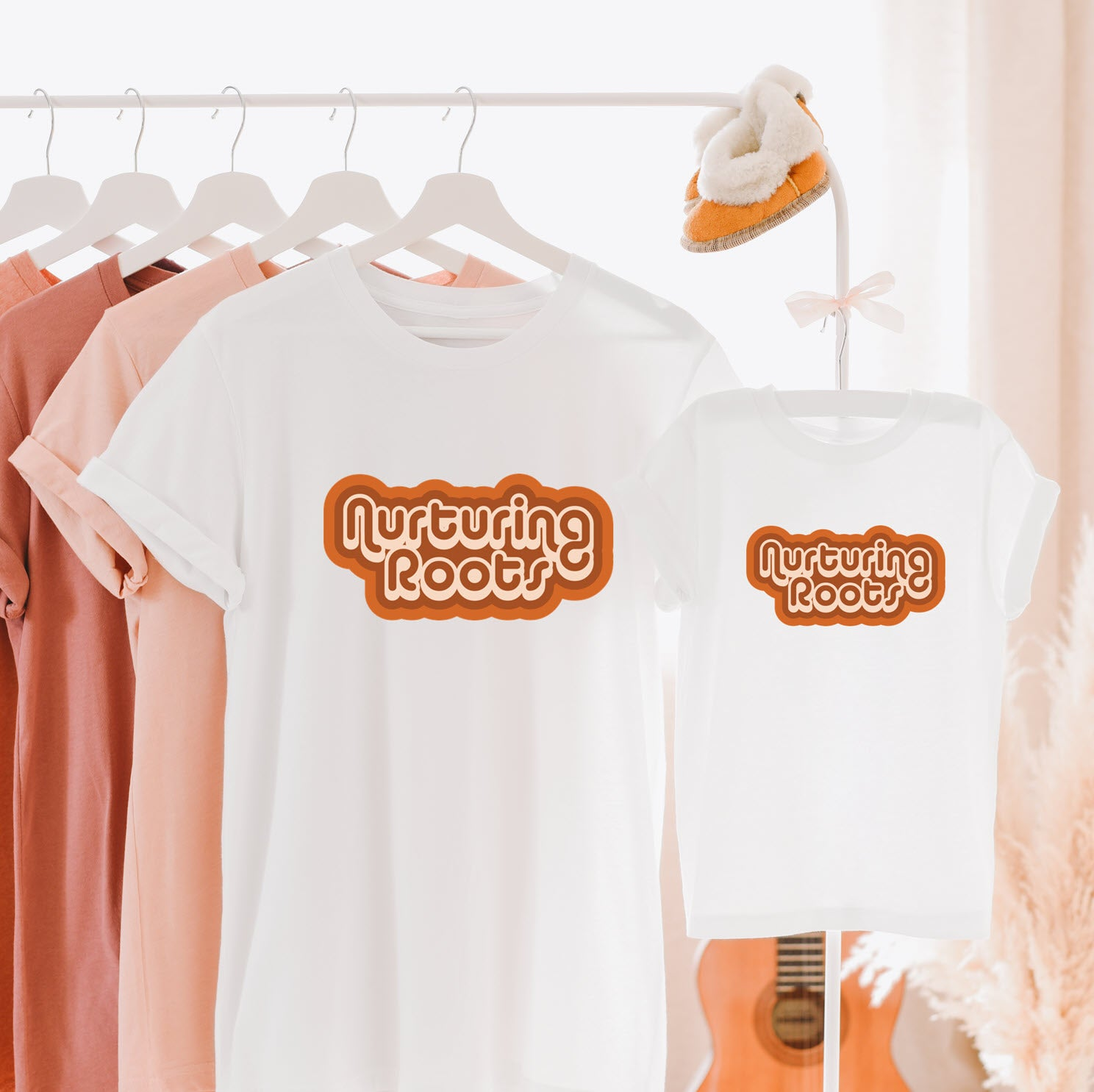Hang lay of matching mommy and me tee shirts printed with the words nurturing roots in a retro style font