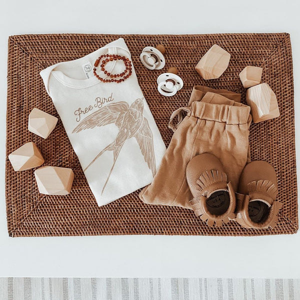 flat lay of a baby outfit with a bodysuit printed with a flying swallow and the words free bird, a pair of tan colored pants, tan colored leather fringe moccasins, two pacifiers, and six wooden abstract shaped blocks