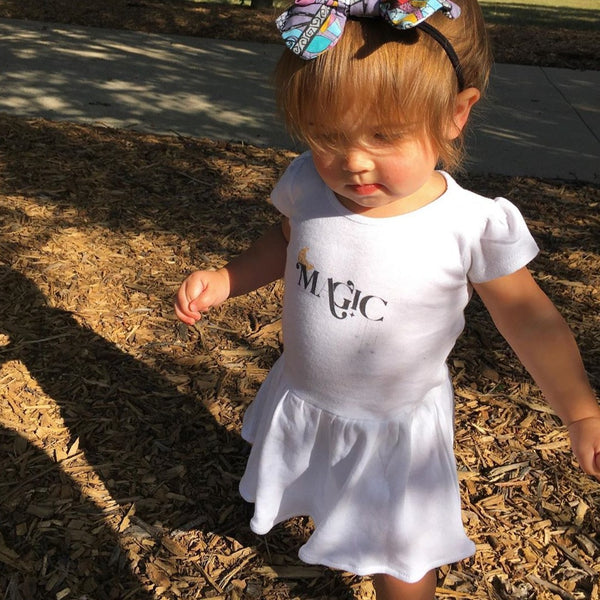 baby girl wearing a white dress printed with the word magic and a yellow crescent moon