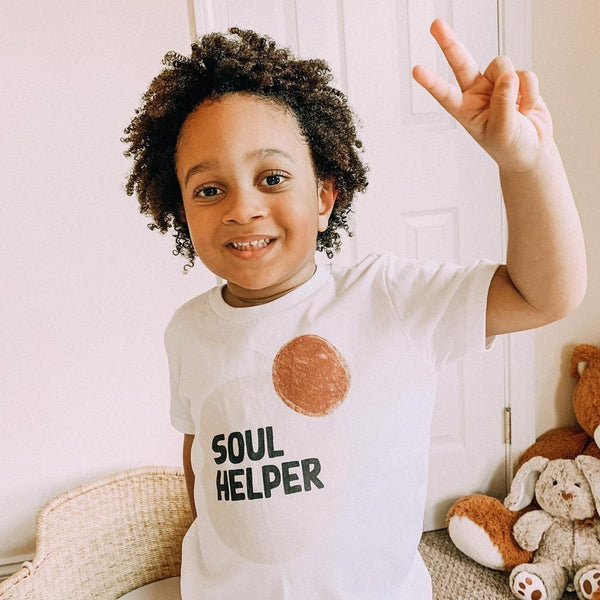 Smiling toddler boy holding up a peace sign, wearing a white tee shirt printed with abstract, neutral colored circles and the words Soul Helper
