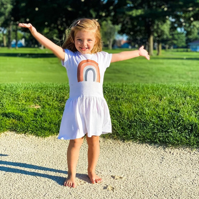 Little girl standing outside with her arms outstretched, wearing a white dress printed with an earth colored rainbow