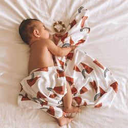 sleeping baby, wrapped in a minky blanket printed with rust colored triangles and black, abstract rainbows