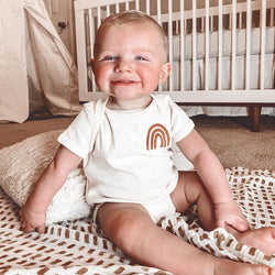 smiling baby boy wearing a bodysuit printed with a rust colored rainbow