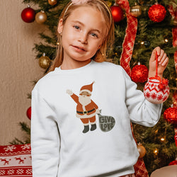 little girl standing in front of a Christmas tree. She is holding up a round, knit ornament, and wearing a white sweatshirt printed with a vintage Santa clause illustration and the words Give Love