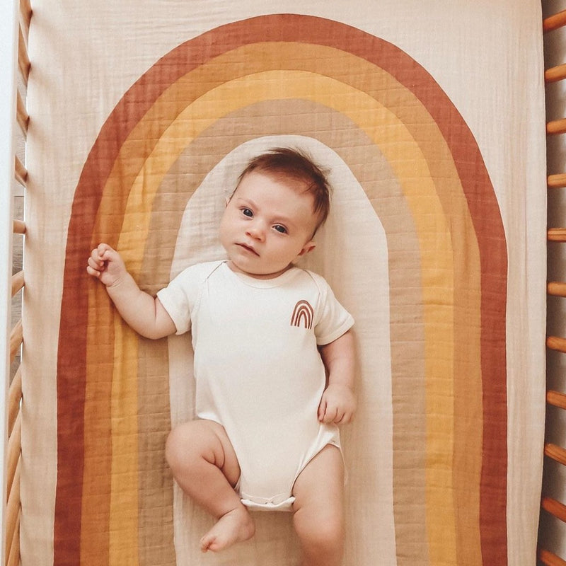 baby laying in a crib with a rainbow crib sheet, and a rust colored rainbow bodysuit