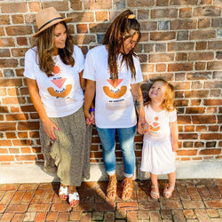 mom and her two daughters standing in front of a brick wall wearing matcihng tee shirts printed with a sun, abstract chapes, and the words we rise, we heal, we overcome