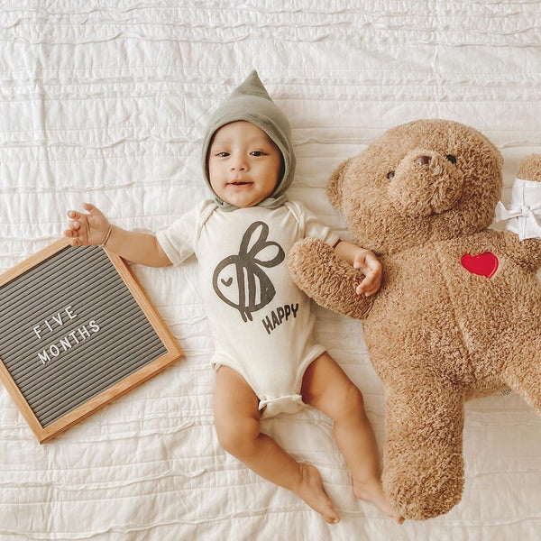 baby wearing a bodysuit printed with a bee and the word Happy, with a Five Months sign and large teddy bear