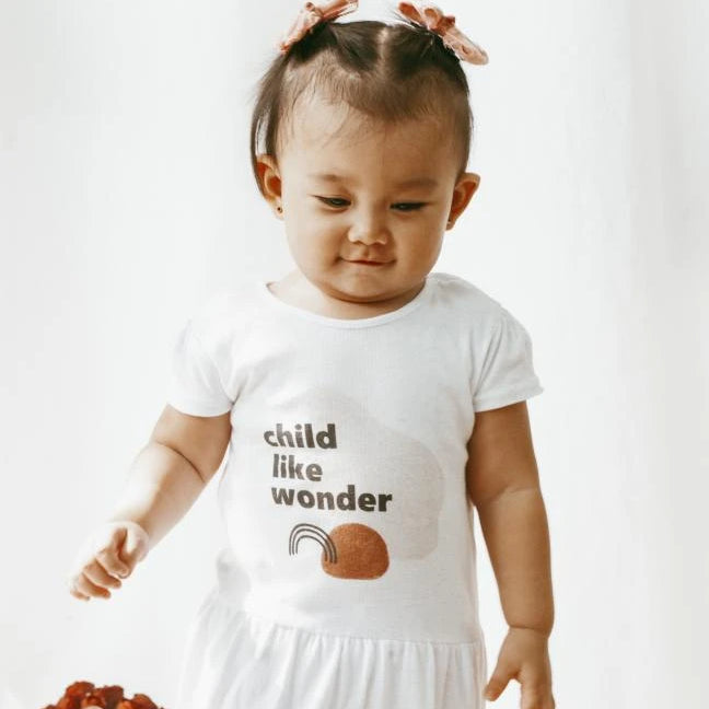 toddler wearing a white dress with the words child like wonder, a black rainbow, and an orange circle on it