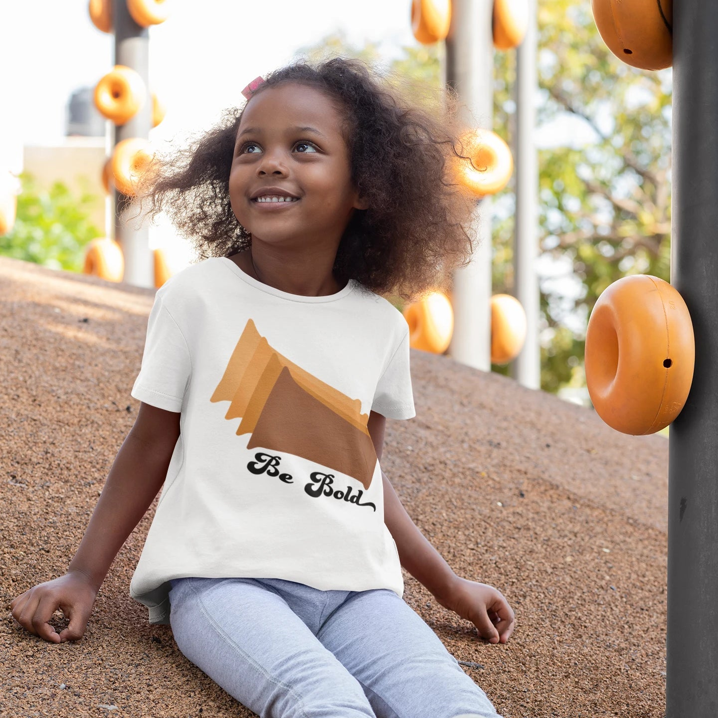 child wearing a white shirt with brown rectangles and the words be bold on it