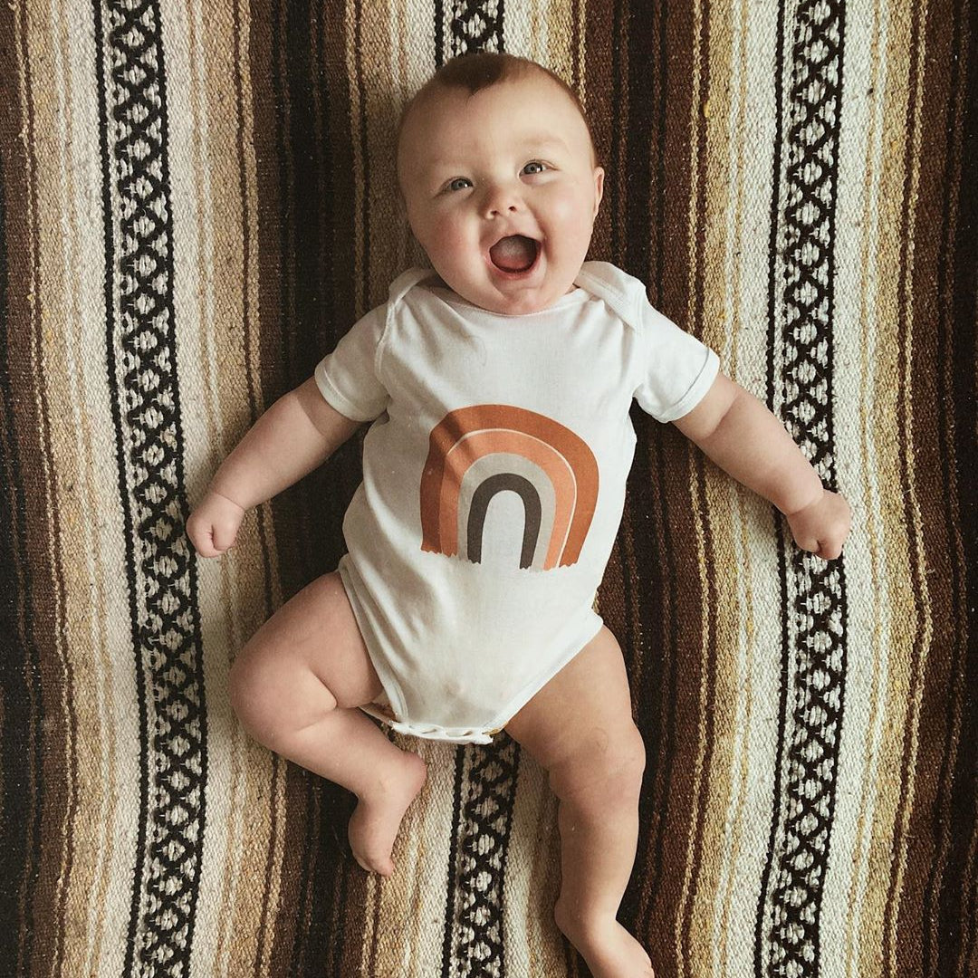 A baby wearing a white bodysuit with a rainbow on it while laying on a striped blanket