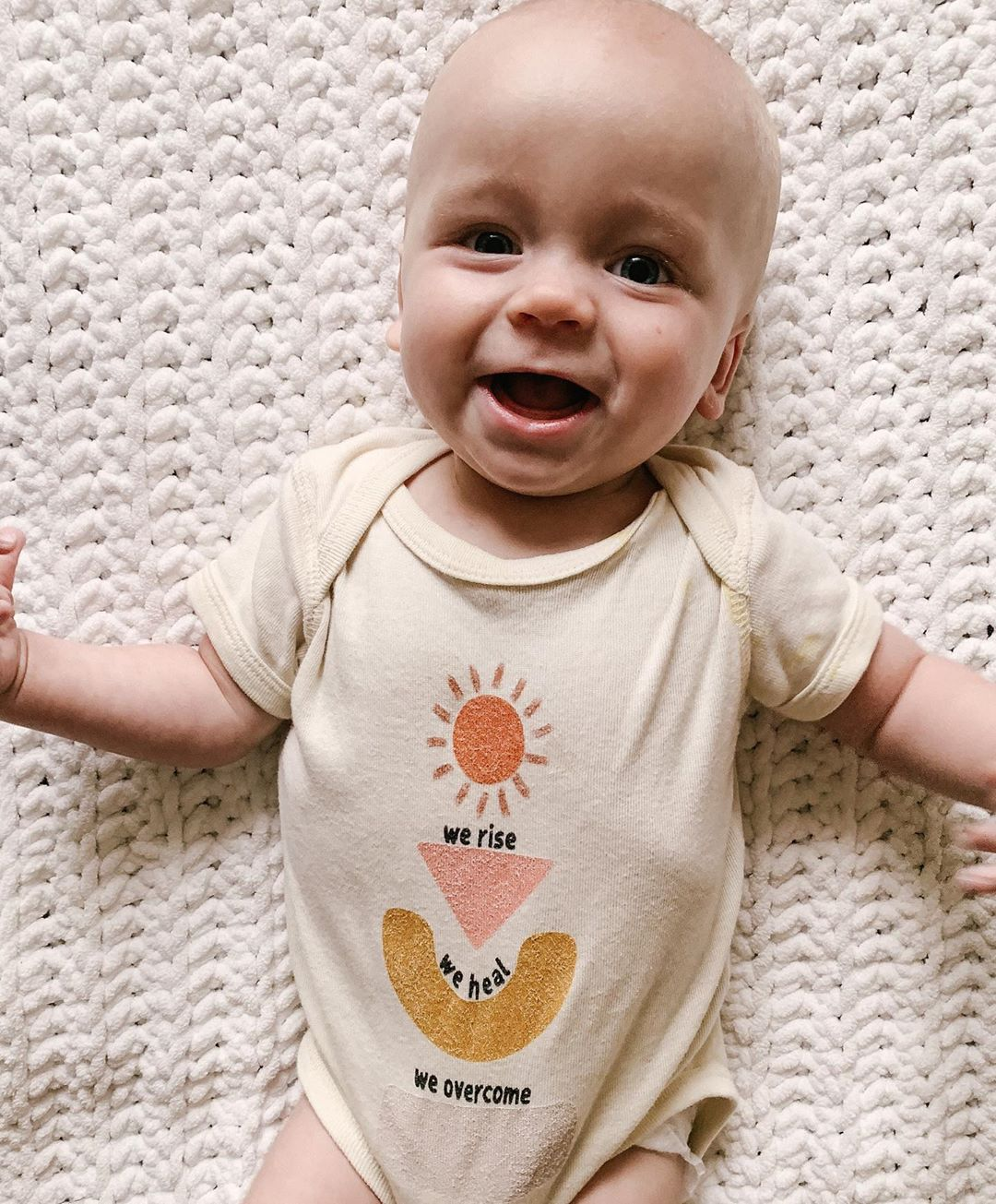 smiling baby wearing a bodysuit printed with we rise we heal we overcome