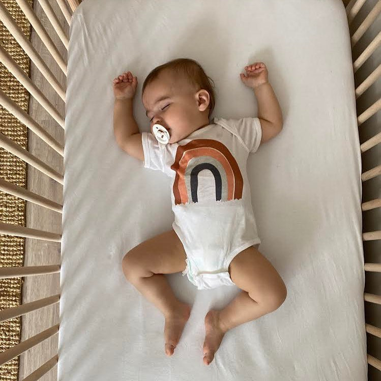 A baby sleeping in a crib and wearing a white bodysuit with a rainbow on it