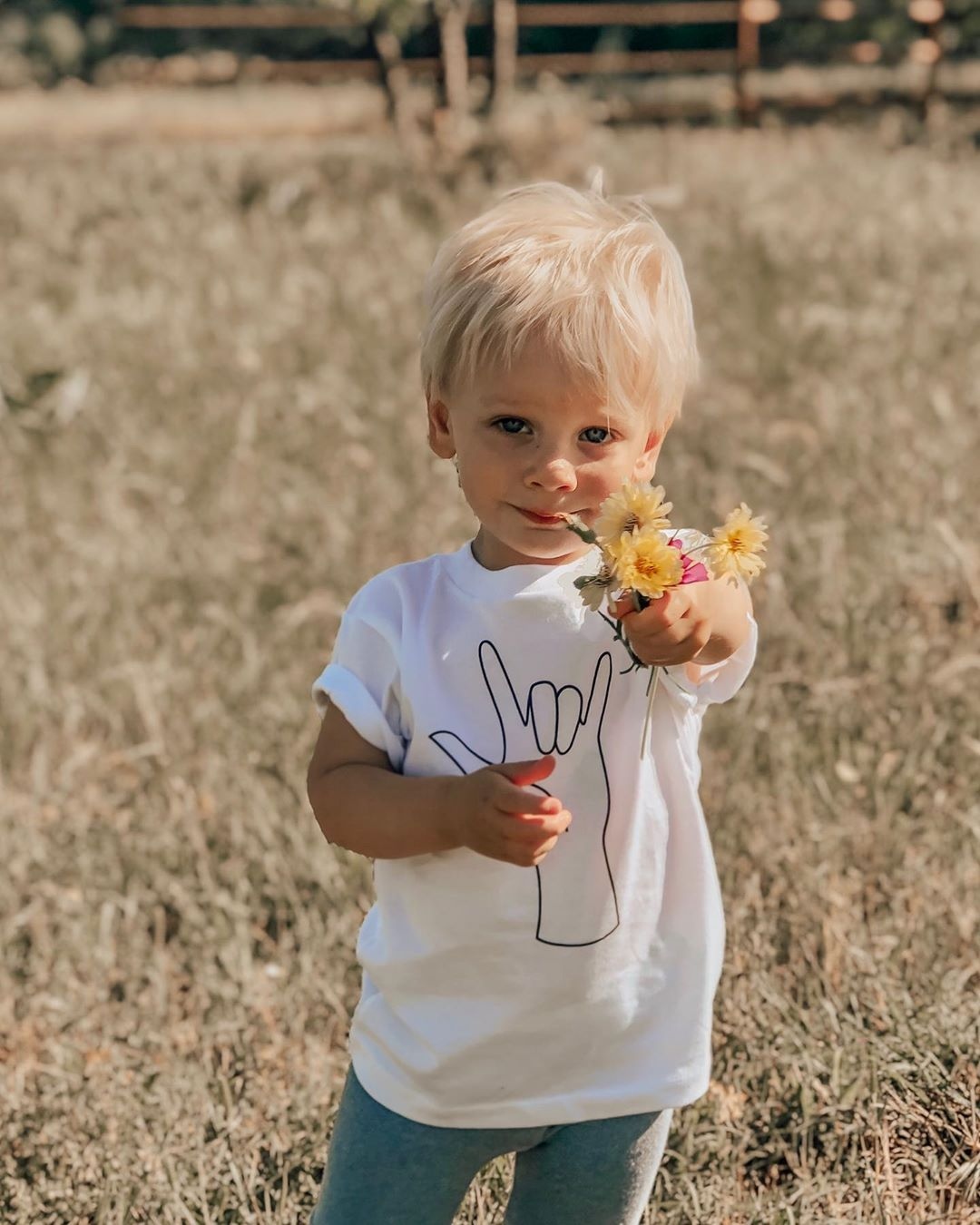 little boy standing in a field, holding out a bouquet of flowers, and wearing a white tee shirt printed with the ASL sing for I love you