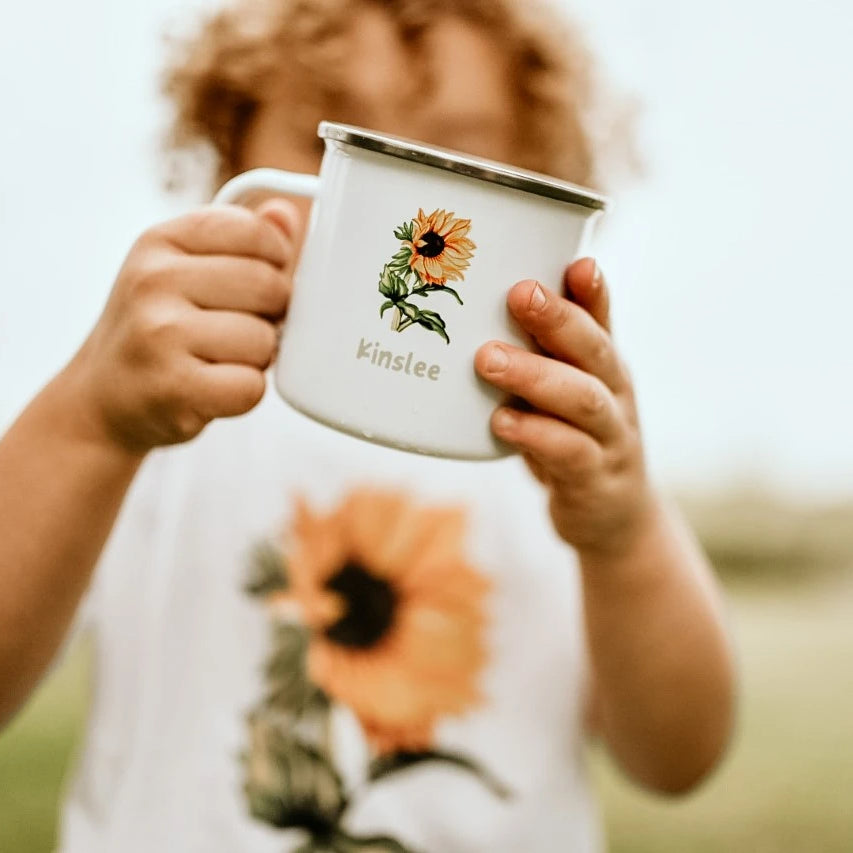 toddler holding a white mug with a sunflower and the name Kinslee on it