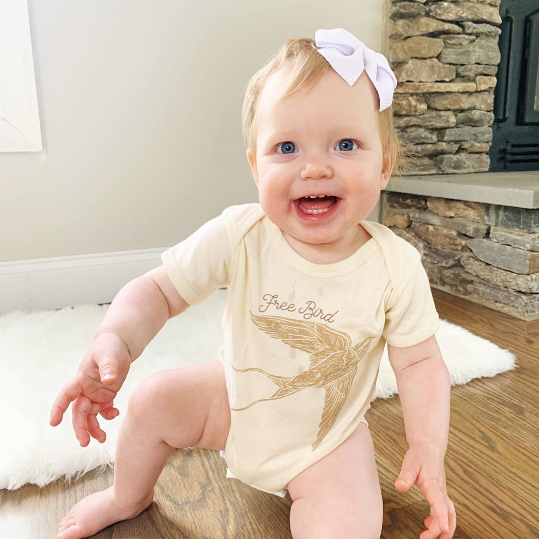 baby wearing a white bodysuit with a bird and the words free bird on it