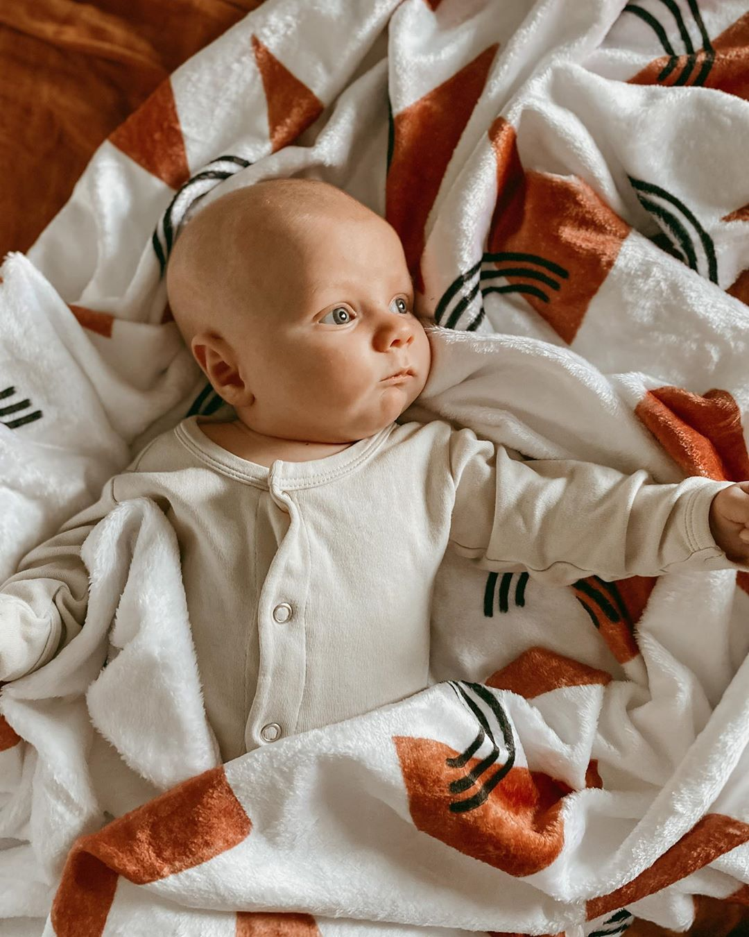 baby laying on a blanket printed with rust colored triangles and black rainbows