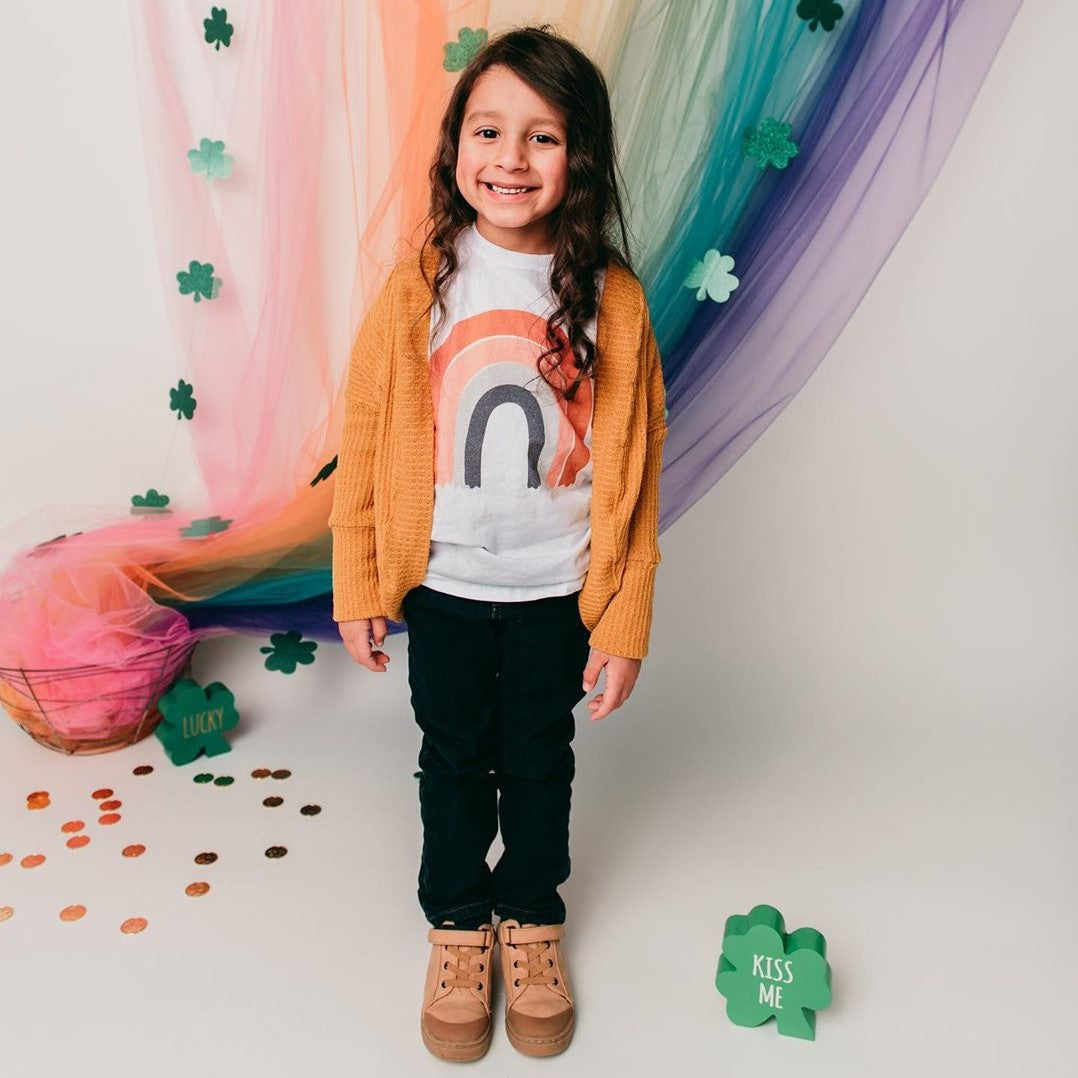 Toddler wearing a white tee shirt with a rainbow on it