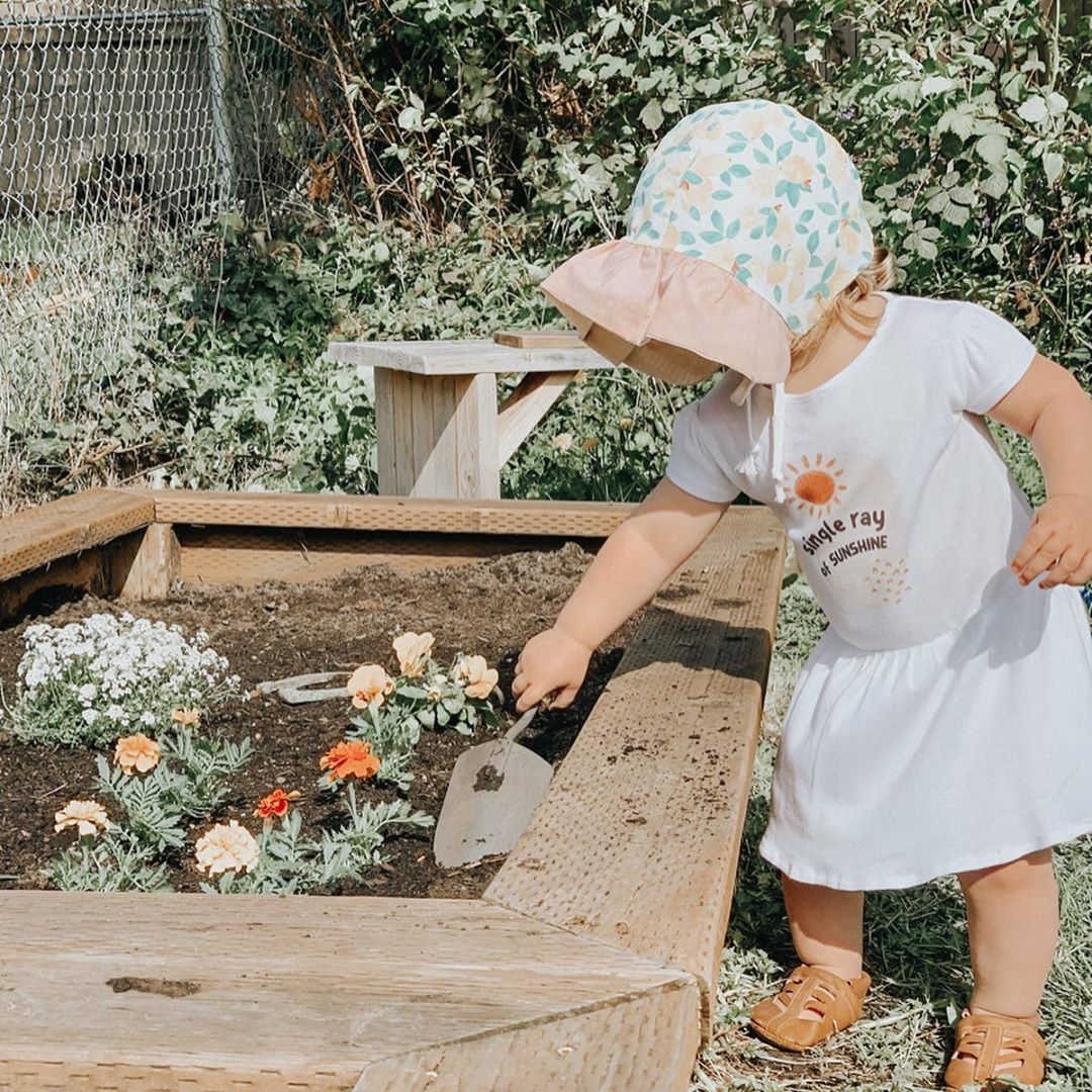 little girl wearing a floral bonnet planting flowers and wearing a dress printed with the words single ray of sunshine