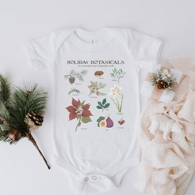 A white bodysuit that says holiday botanicals on top and has pictures of plants in the middle