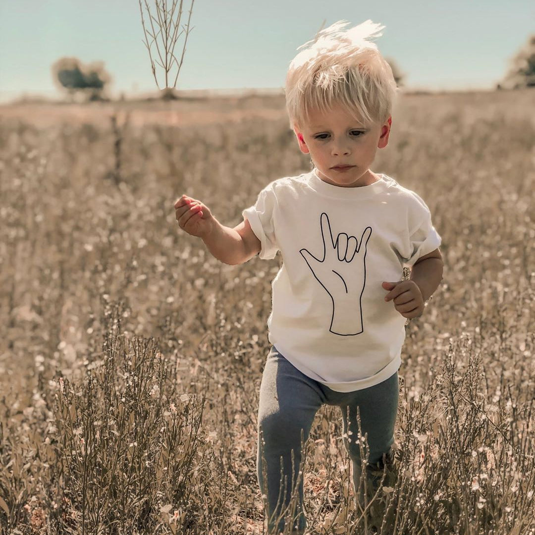 toddler wearing a white shirt with the ASL sign for I love you on it while walking through tall grass