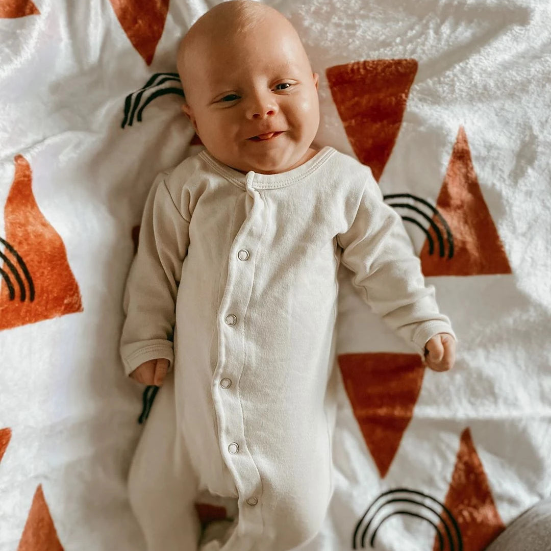 baby laying on a blanket with orange triangles and black rainbows on it