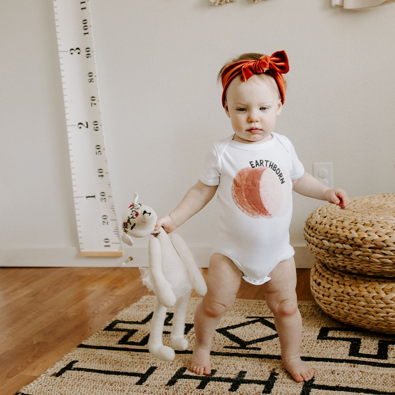 toddler wearing a white bodysuit with a brown circle and the word earthborn on it
