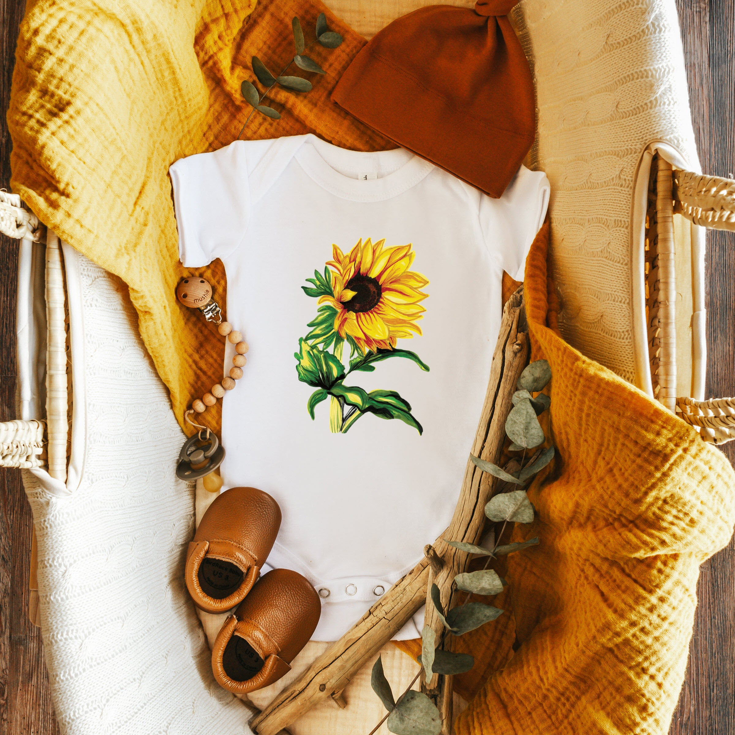 A white bodysuit with a sunflower on it