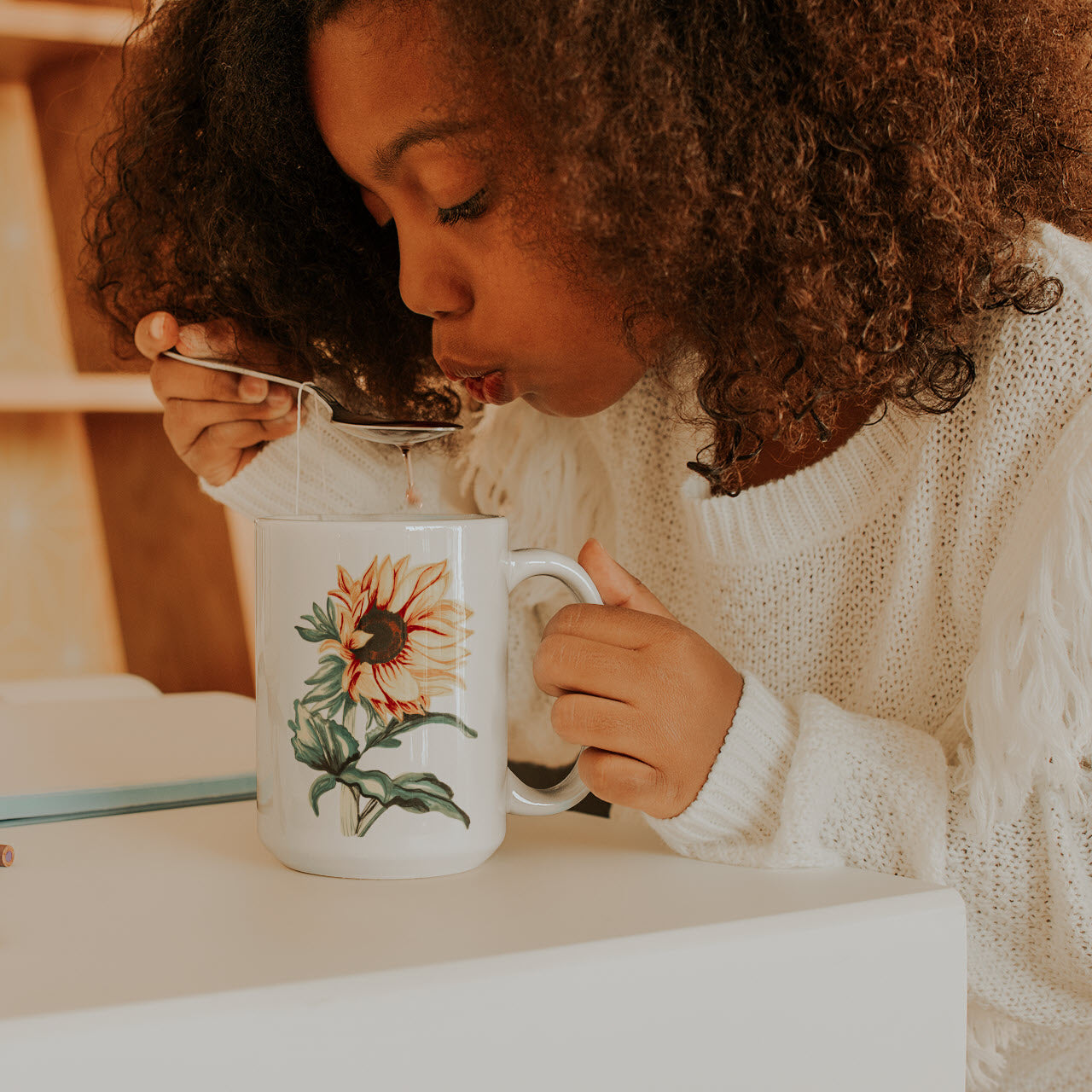 woman drinking out of a mug with a sunflower on it
