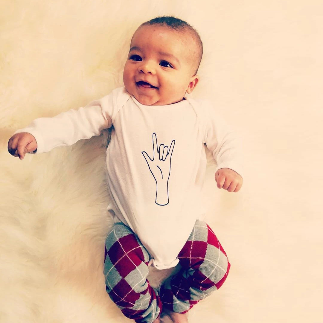 baby wearing a white bodysuit with the ASL sign for I love you on it