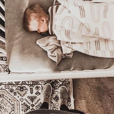 a baby sleeping while wrapped in a white blanket with faded gray rainbows on it