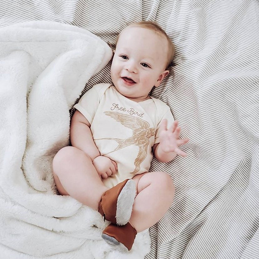 smiling baby wearing a bodysuit printed with a bird and the words free bird
