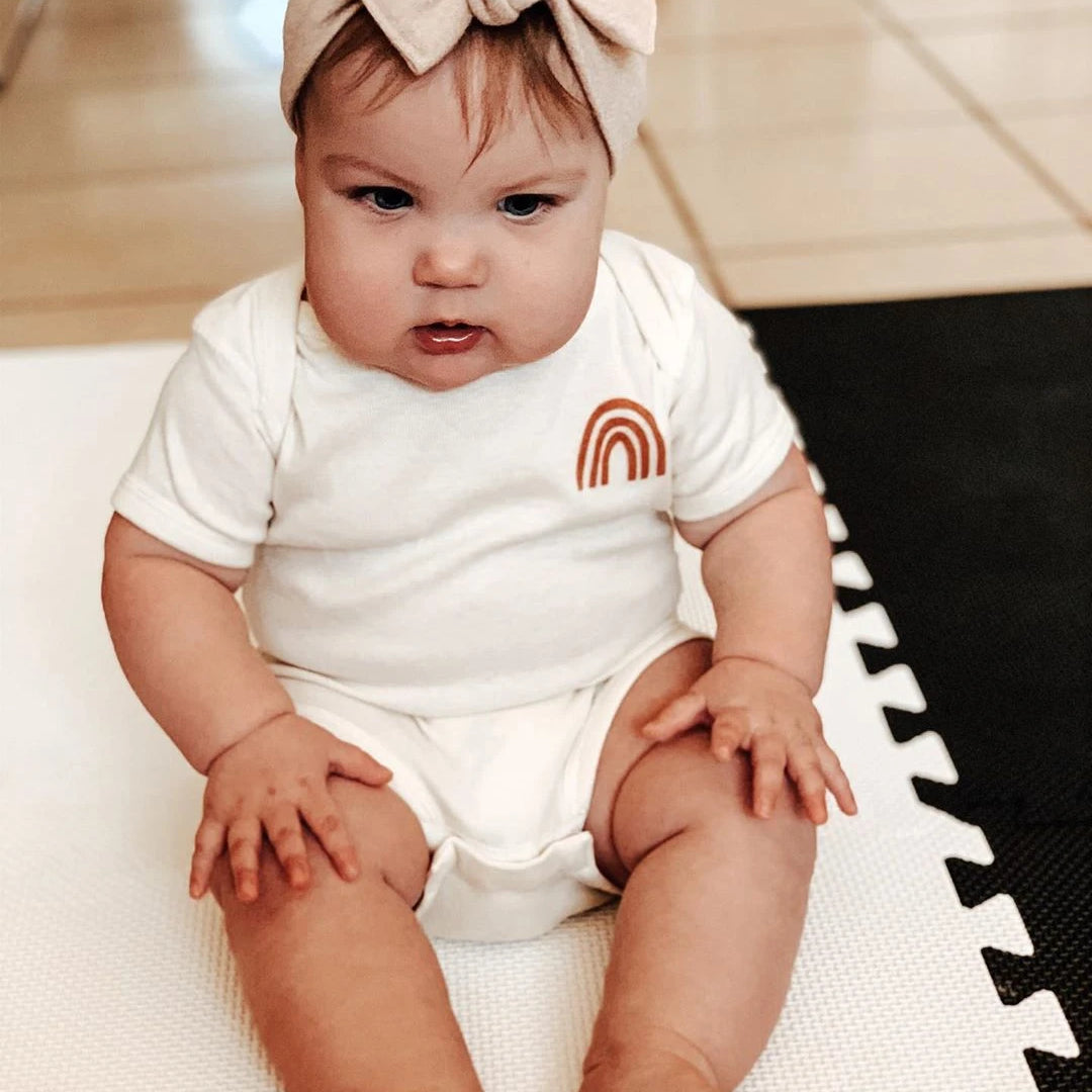toddler wearing a white bodysuit with a small orange rainbow on it