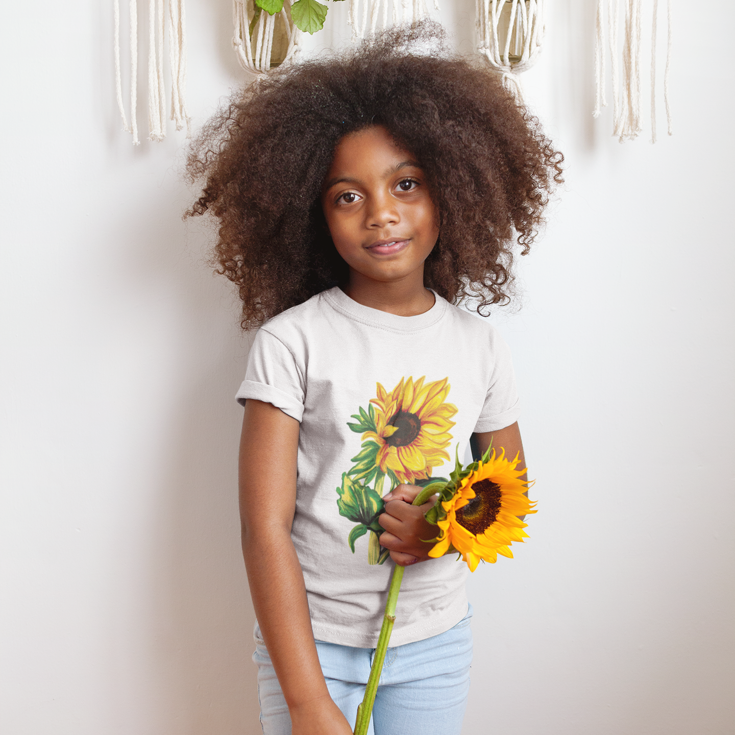 little girl wearing a shirt printed with a sunflower and holding a sunflower