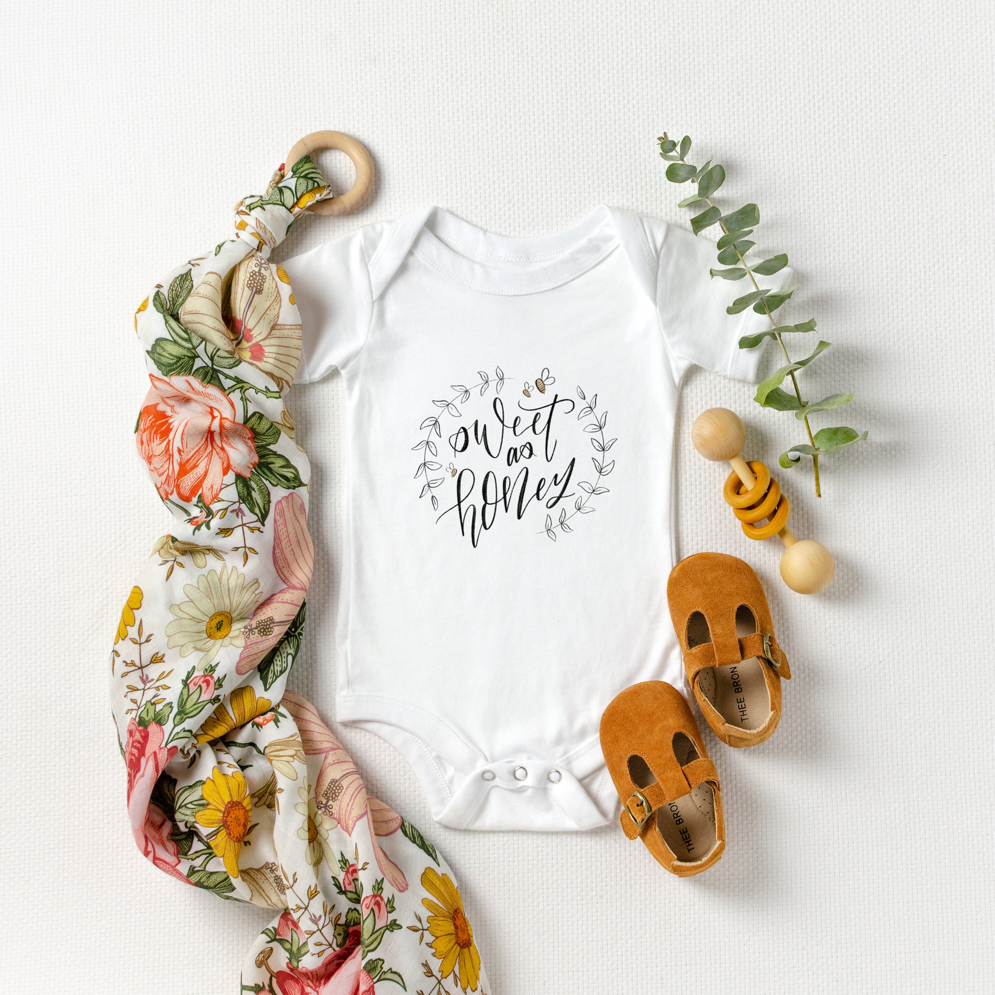 White baby bodysuit printed with the words sweet as honey