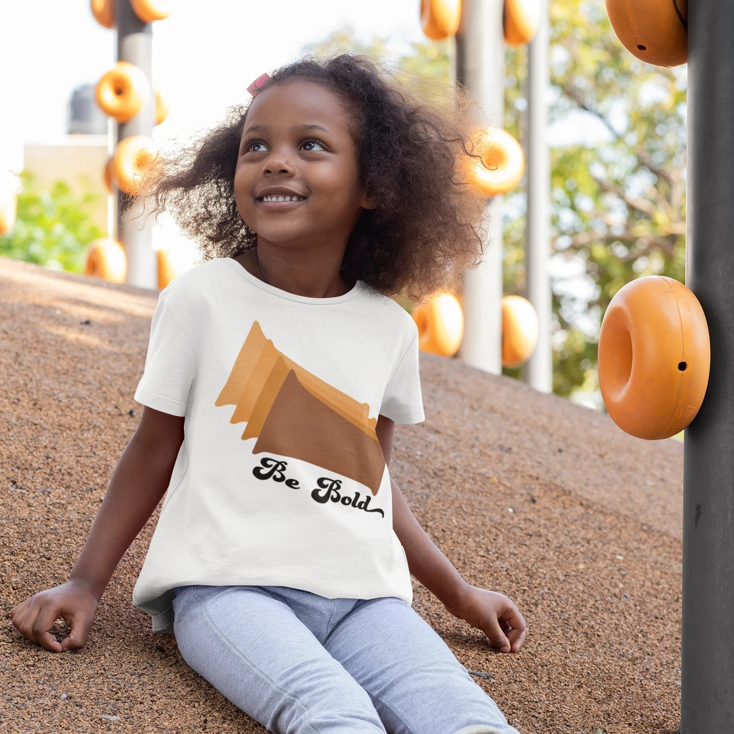 A toddler wearing a white tee shirt with brown rectangles an the words be bold on it