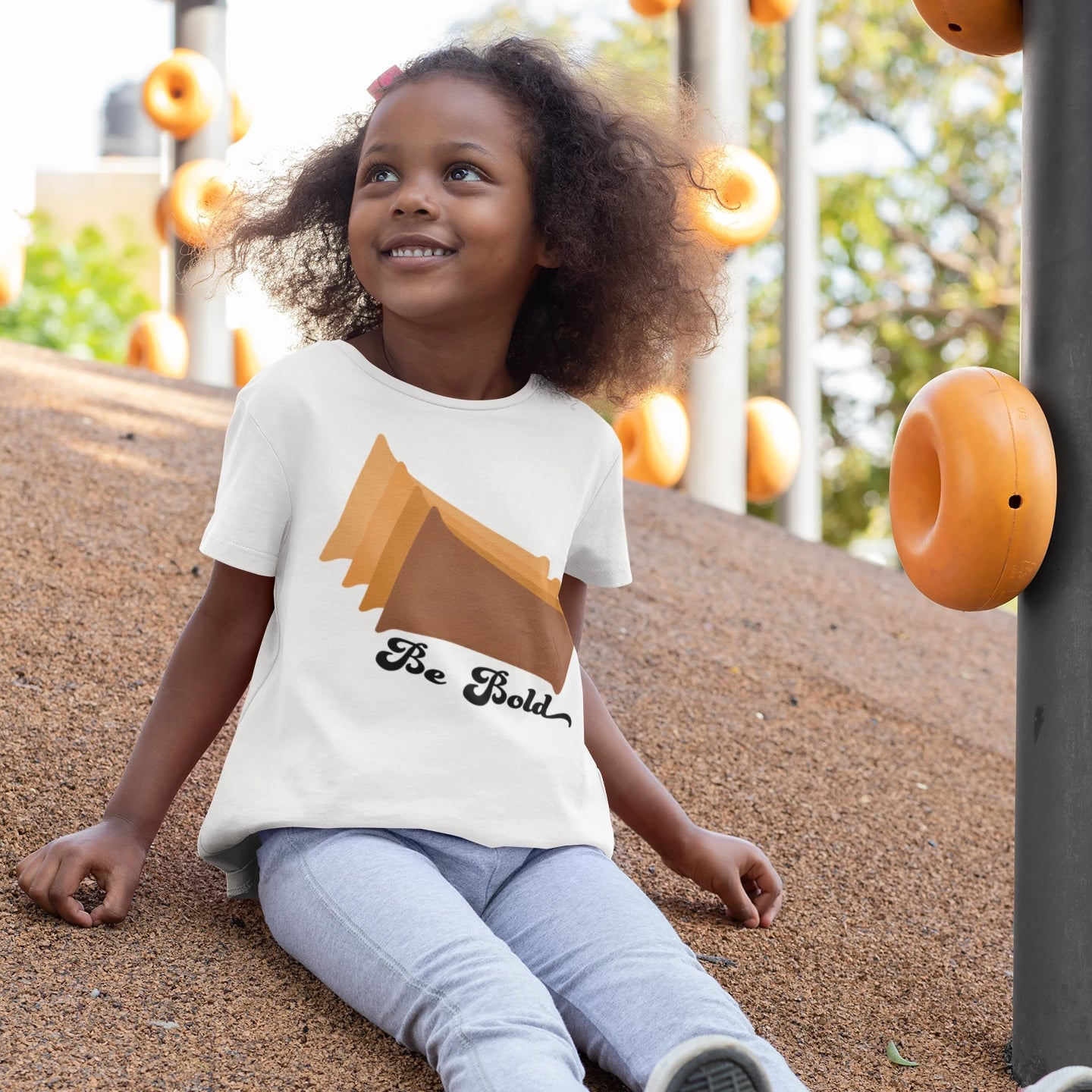 toddler wearing a white tee shirt with brown rectangles and the words be bold on it
