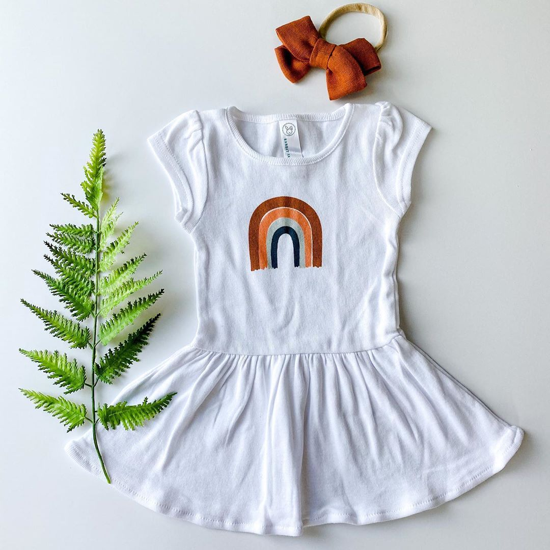 white baby dress printed with a rainbow