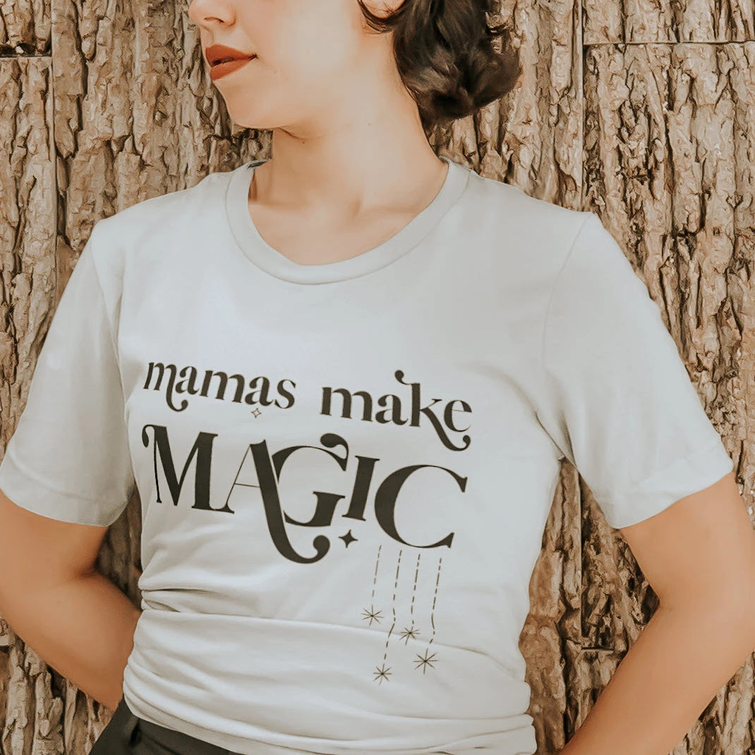 A woman wearing a white tee shirt with the words mamas make magic on it