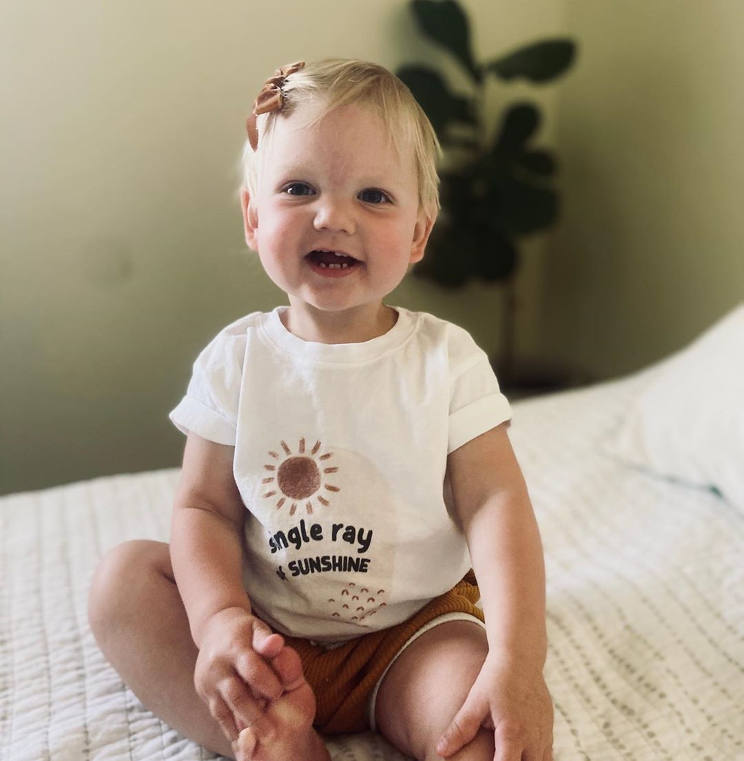 toddler wearing a white tee shirt that says single ray of sunshine on it