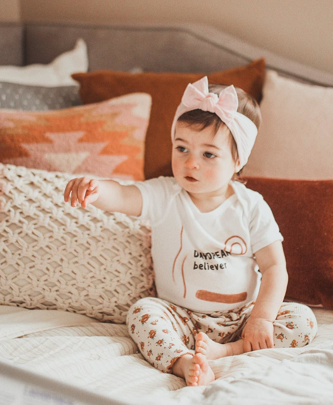 baby girl sitting on a bed and pointing. She's wearing a bodysuit printed with Daydream Believer